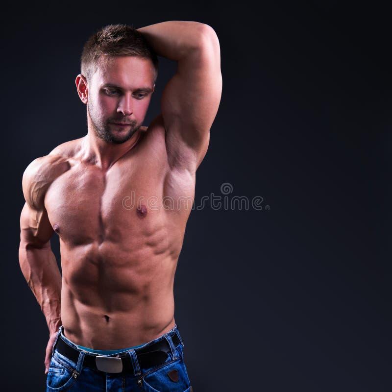 Giovane uomo muscolare che posa sopra il fondo scuro con lo spazio della copia fotografia stock libera da diritti