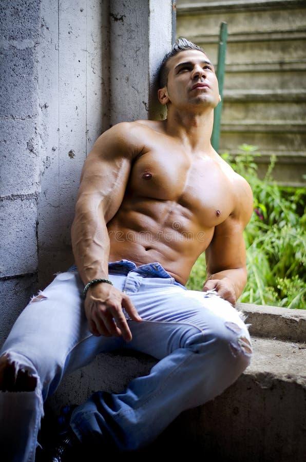 Giovane uomo muscolare del latino senza camicia in jeans che si siedono contro il muro di cemento immagine stock