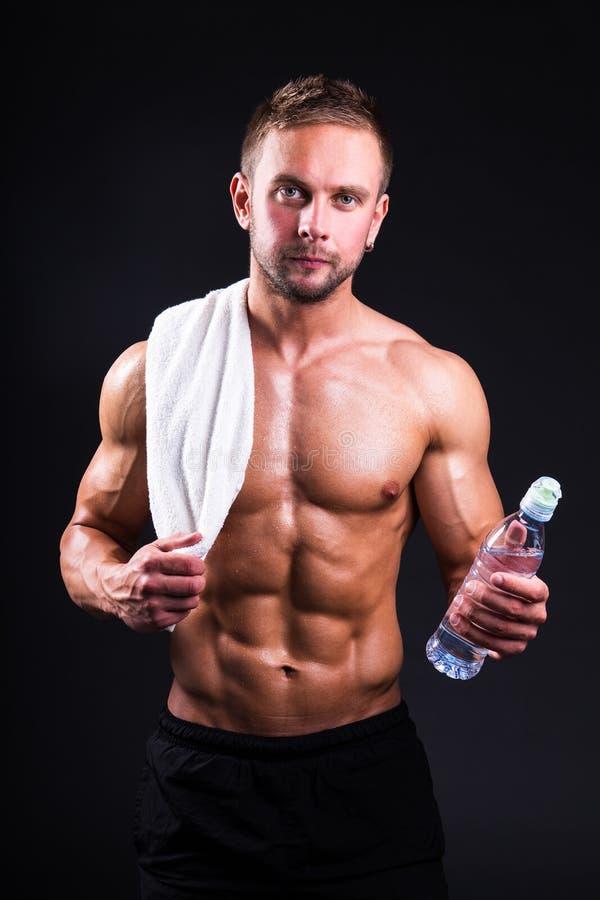 Giovane uomo muscolare dopo la formazione con l'asciugamano ed acqua sopra grey fotografia stock