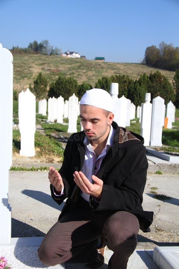 Giovane uomo musulmano vicino alla sua tomba del padre immagini stock libere da diritti