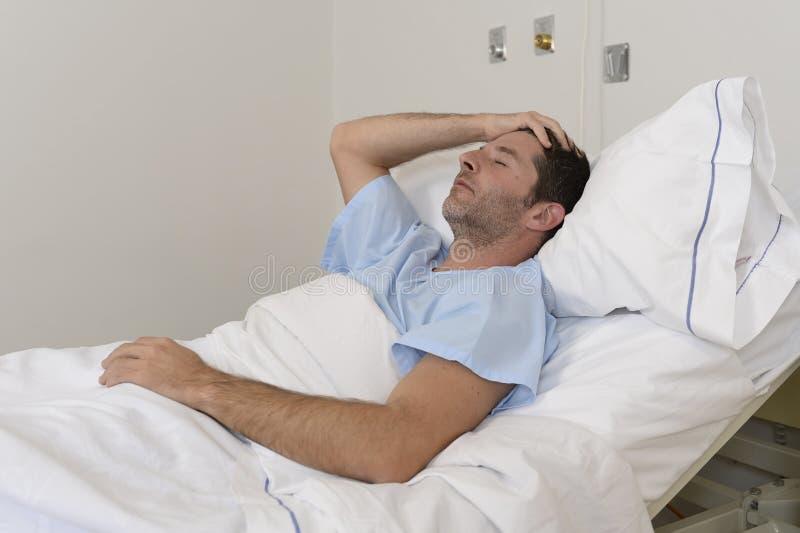 Giovane uomo paziente che si trovano al letto di ospedale che riposa sguardo stanco triste e depresso preoccupato fotografia stock libera da diritti