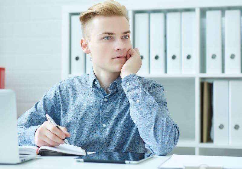 Giovane uomo pensieroso di affari che si siede al dask con il computer portatile e che esamina la finestra immagini stock