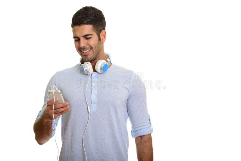 Giovane uomo persiano felice che sorride e che per mezzo del telefono cellulare mentre wea fotografie stock libere da diritti