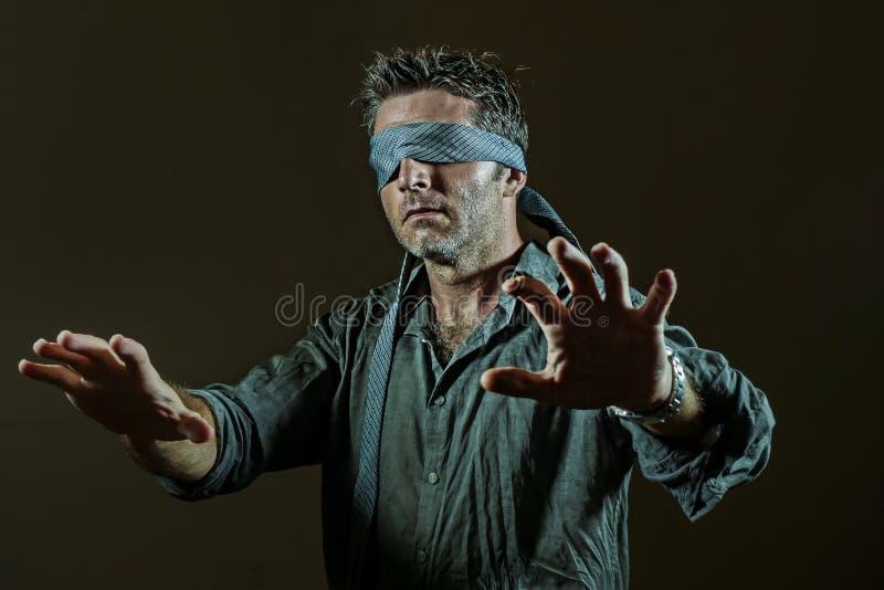 Giovane uomo perso e confuso bendato gli occhi con la cravatta che gioca sfida virale pericolosa di tendenza di Internet con i ci fotografie stock