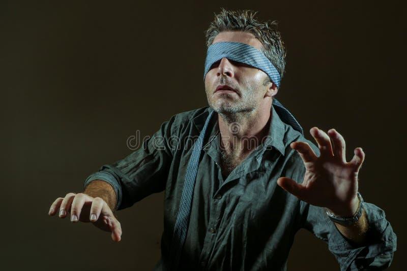 Giovane uomo perso e confuso bendato gli occhi con la cravatta che gioca sfida virale pericolosa di tendenza di Internet con i ci fotografie stock libere da diritti