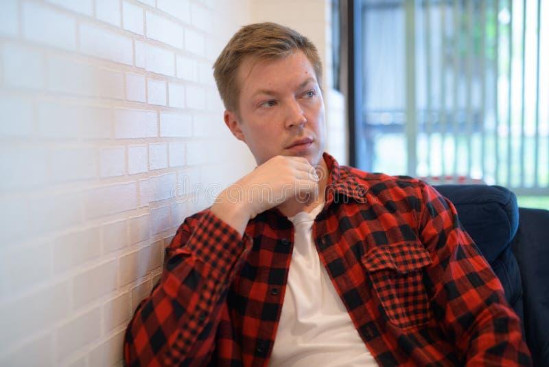 Giovane uomo premuroso dei pantaloni a vita bassa che esamina attraverso la finestra la caffetteria immagine stock