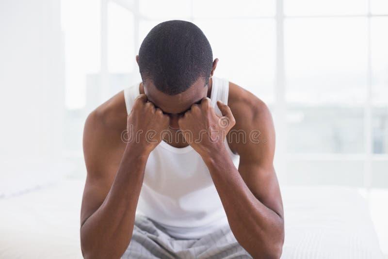 Giovane uomo premuroso di afro che si siede sul letto immagini stock libere da diritti