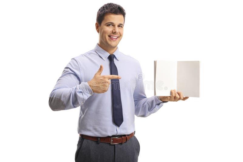 Giovane uomo professionale che tiene un taccuino con le pagine in bianco ed indicare immagini stock