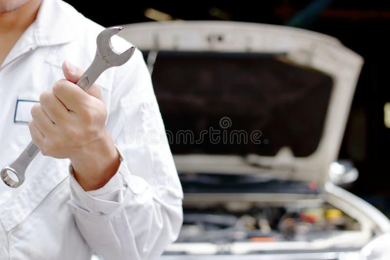 Giovane uomo professionale del meccanico in chiave uniforme della tenuta con il cappuccio aperto al garage di riparazione Concett fotografie stock