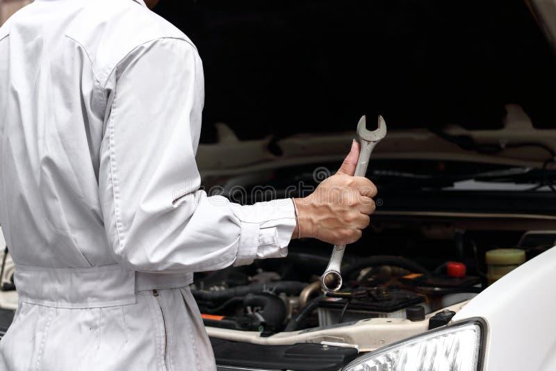 Giovane uomo professionale del meccanico in uniforme con la chiave che diagnostica motore contro il cappuccio aperto al garage di fotografie stock