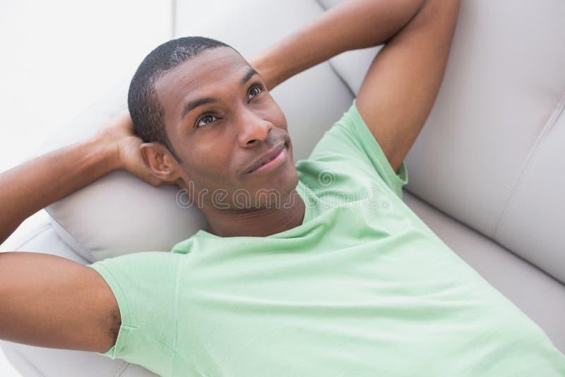 Giovane uomo rilassato premuroso di afro che si trova sul sofà immagine stock libera da diritti