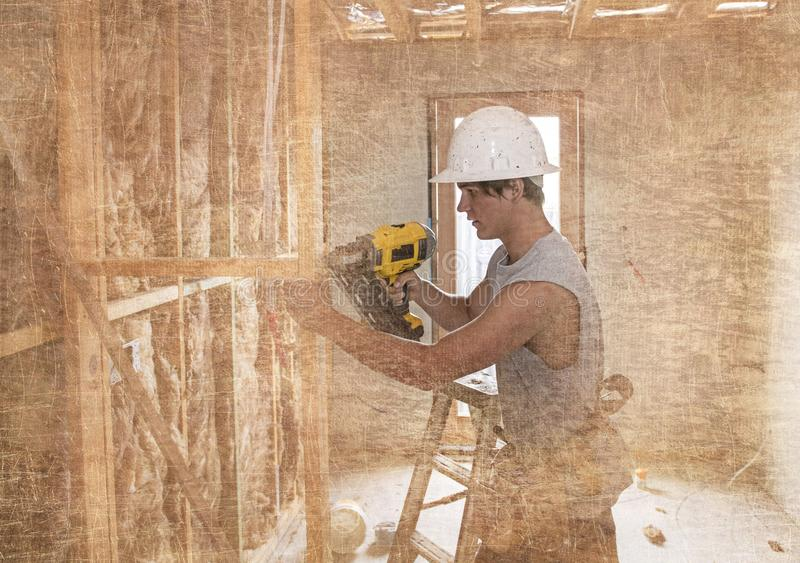 Giovane uomo 20s dell'apprendista di industria del costruttore sul casco protettivo che impara lavoro con il trapano al sito indu immagini stock libere da diritti