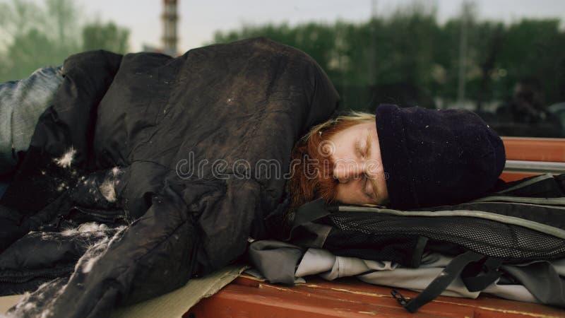 Giovane uomo senza tetto che prova a dormire sotto il rivestimento sul banco al marciapiede fotografia stock libera da diritti