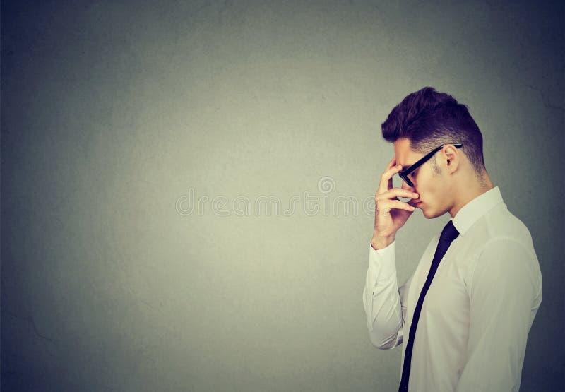 Giovane uomo serio di affari che pensa molto duro fotografie stock