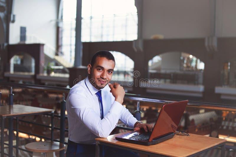 Giovane uomo sicuro bello di affari che lavora al computer portatile al caffè, luce del chiarore Pausa caffè, concetto di affari immagini stock