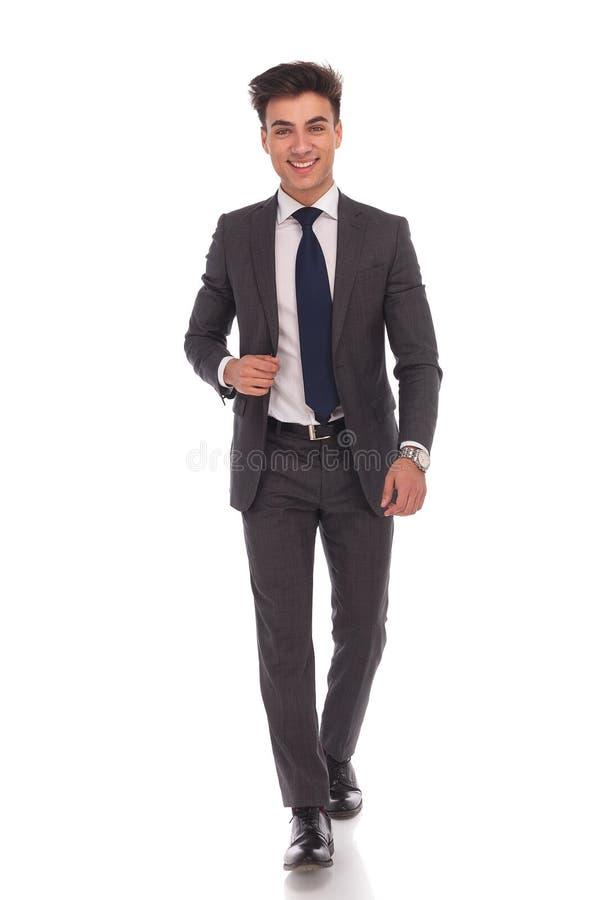Giovane uomo sicuro di affari che ride e che cammina fotografia stock