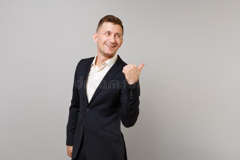 Giovane uomo Smirked di affari in vestito nero classico, camicia indicante pollice da parte dietro la sua parte posteriore isolat immagine stock