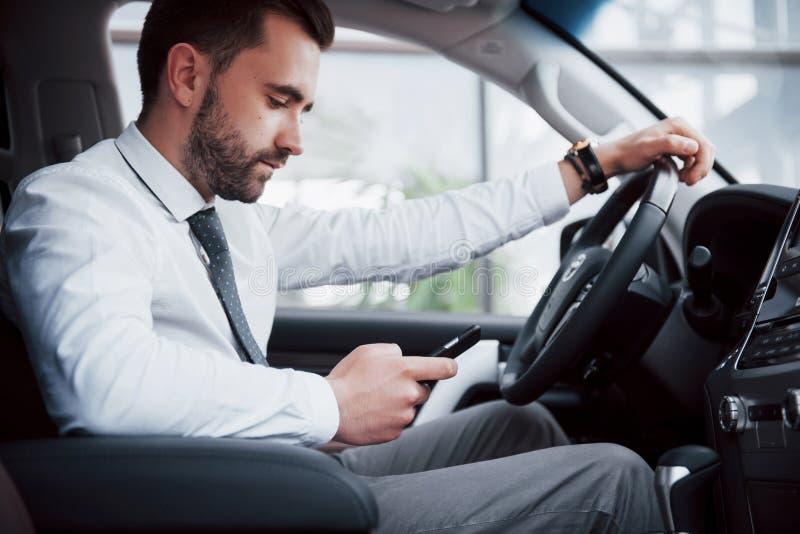 Giovane uomo soddisfatto di affari che esamina telefono cellulare mentre conducendo un'automobile fotografie stock libere da diritti