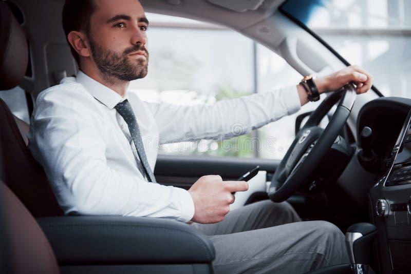 Giovane uomo soddisfatto di affari che esamina telefono cellulare mentre conducendo un'automobile fotografia stock