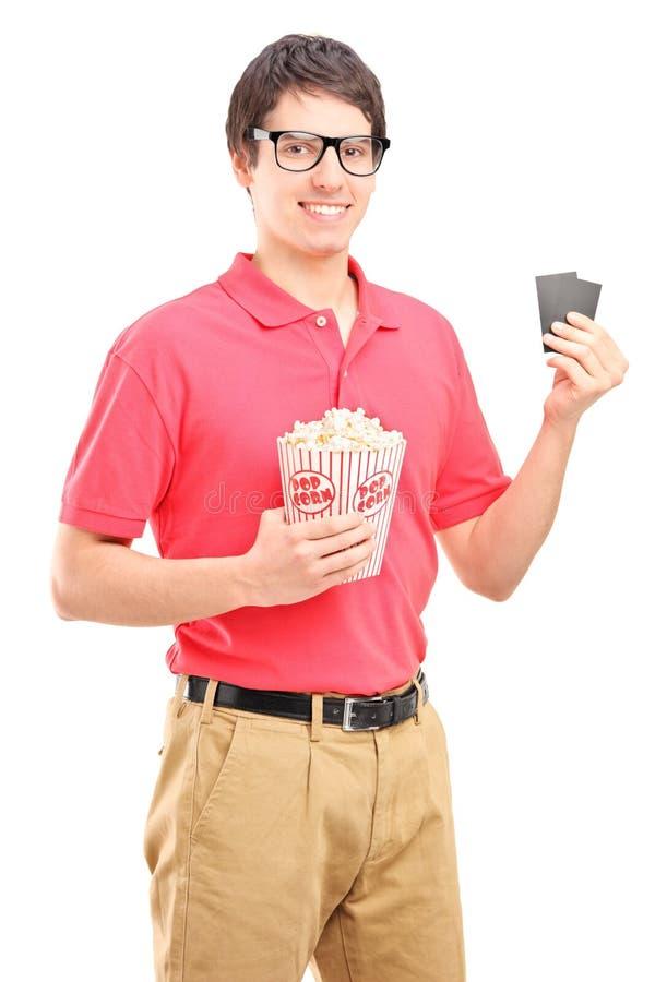 Giovane uomo sorridente che tiene un contenitore di popcorn e due biglietti per il cinematografo immagine stock libera da diritti