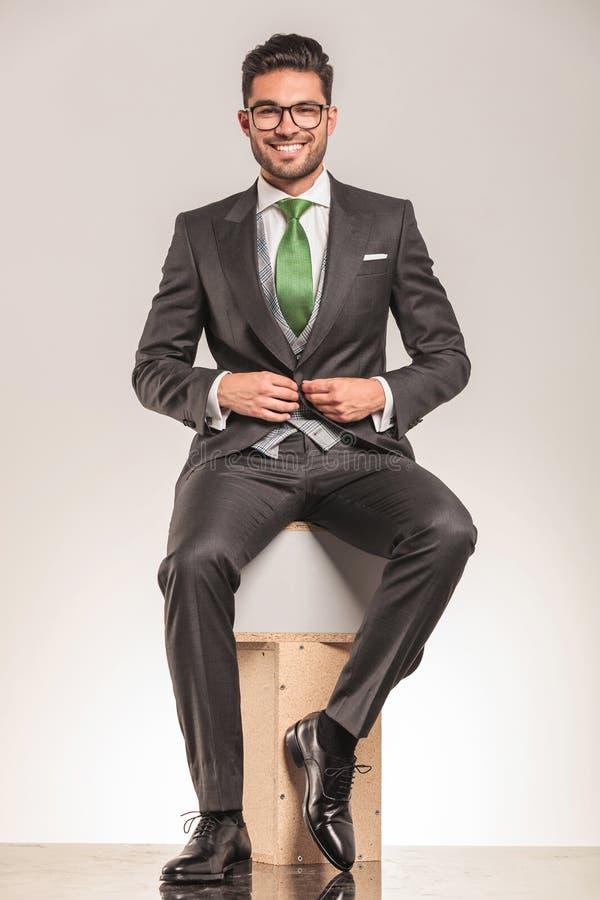 Giovane uomo sorridente di affari che si siede sulle scatole di legno fotografia stock