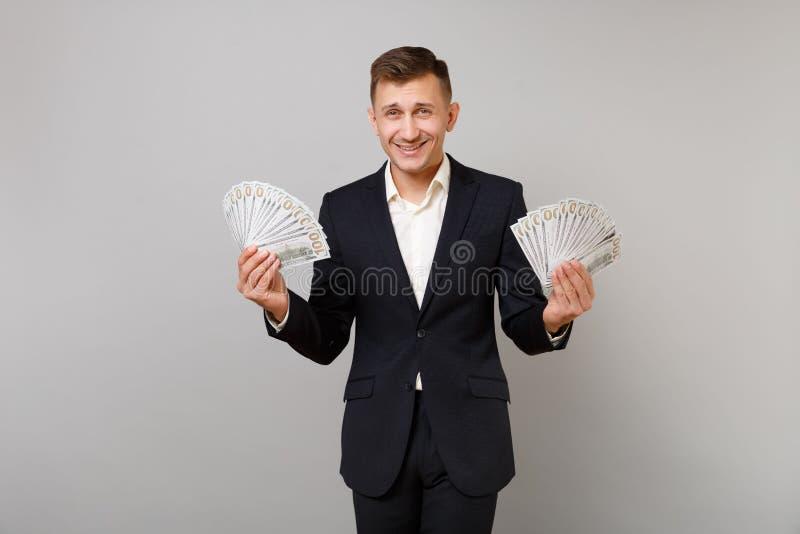 Giovane uomo sorridente di affari in vestito nero classico, camicia che tiene il mazzo di banconote dei dollari, denaro contante  immagine stock libera da diritti