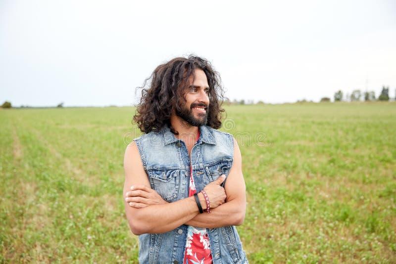 Giovane uomo sorridente di hippy sul campo verde fotografia stock