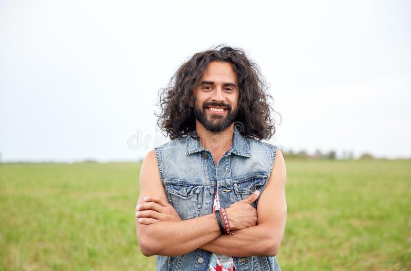 Giovane uomo sorridente di hippy sul campo verde fotografia stock libera da diritti