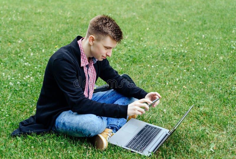 Giovane uomo sorridente nella seduta della camicia e del rivestimento di plaid immagine stock