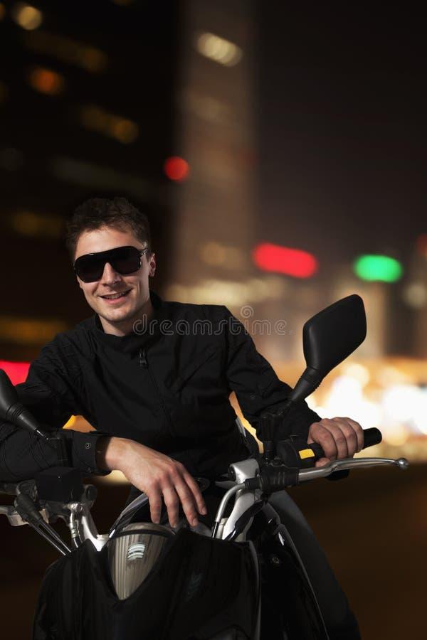 Giovane uomo sorridente in occhiali da sole che si siedono sul suo motociclo alla notte a Pechino fotografia stock