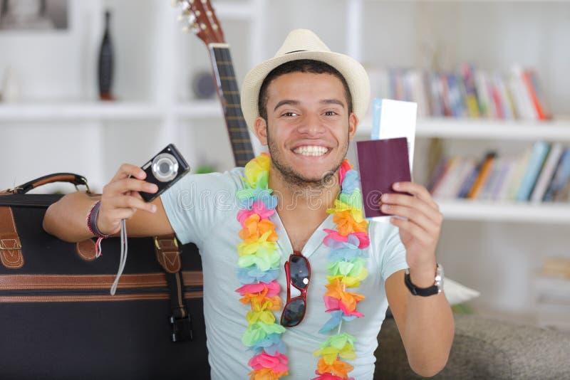 Giovane uomo vietnamita felice con la macchina fotografica digitale ed il passaporto immagini stock