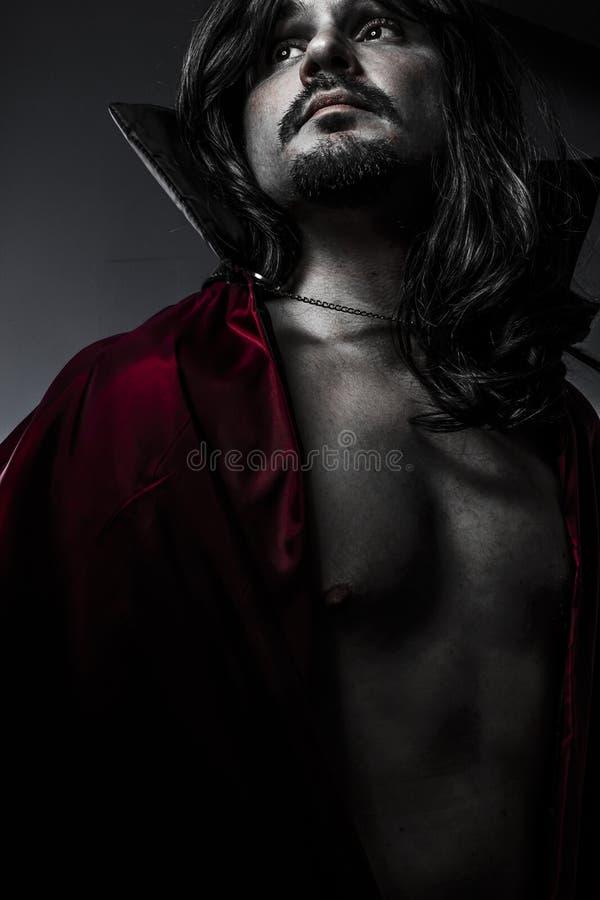 Giovane vampiro sensuale con il cappotto nero ed i capelli lunghi, nudo immagine stock libera da diritti
