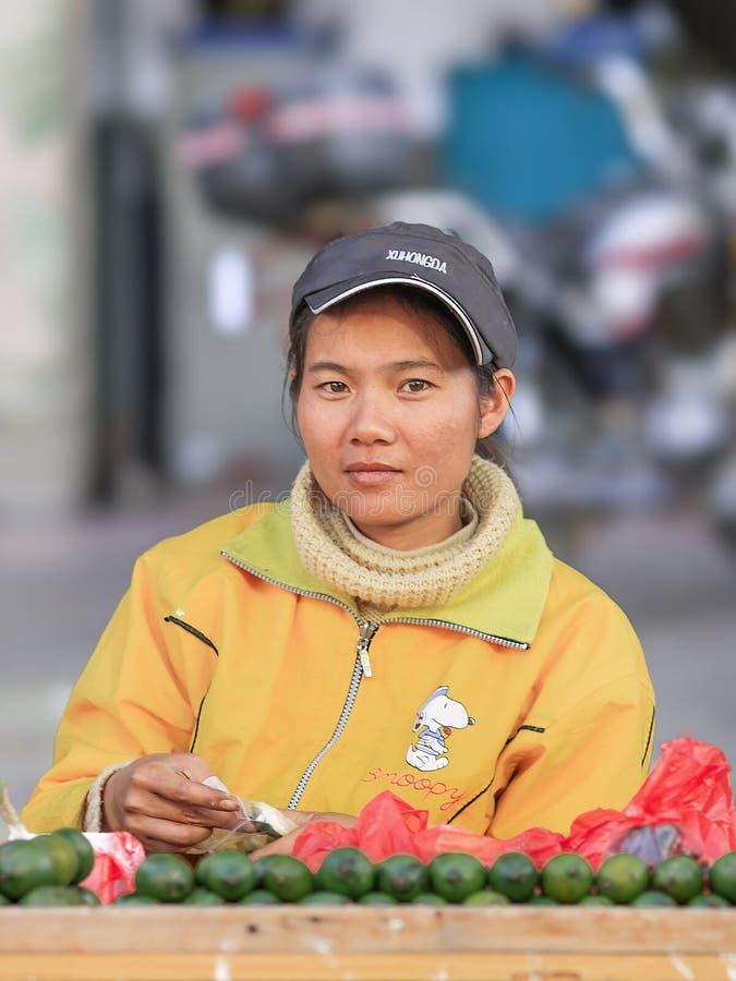 Giovane venditore femminile su un mercato in Lishui, isola di Hainan, Cina immagine stock