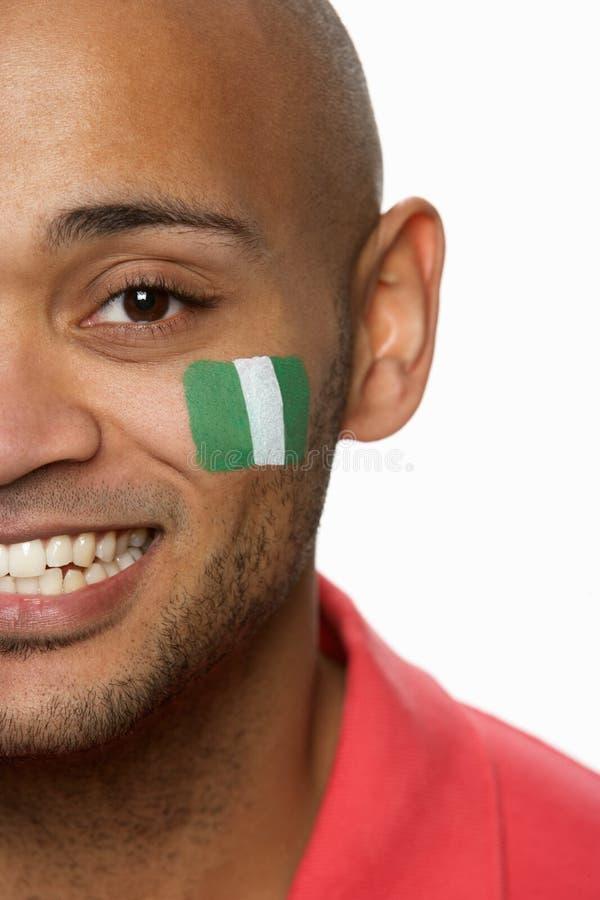 Giovane ventilatore di sport maschio con la bandierina nigeriana immagini stock