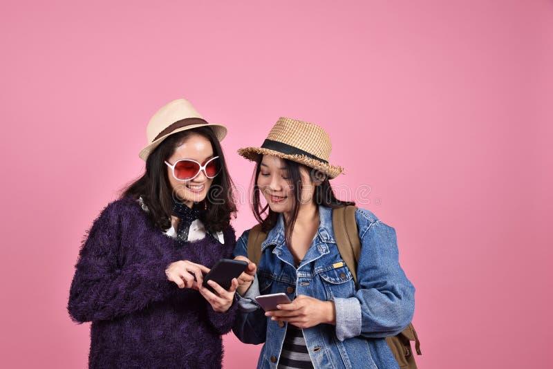 Giovane viaggiatore asiatico che per mezzo dello smartphone mobile, mappa turistica delle amiche che cerca la navigazione fotografia stock libera da diritti