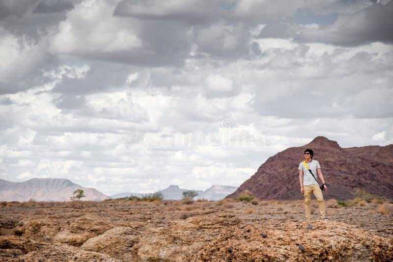 Giovane viaggiatore asiatico dell'uomo che sta sul canyon di Sesriem, Namibia immagini stock