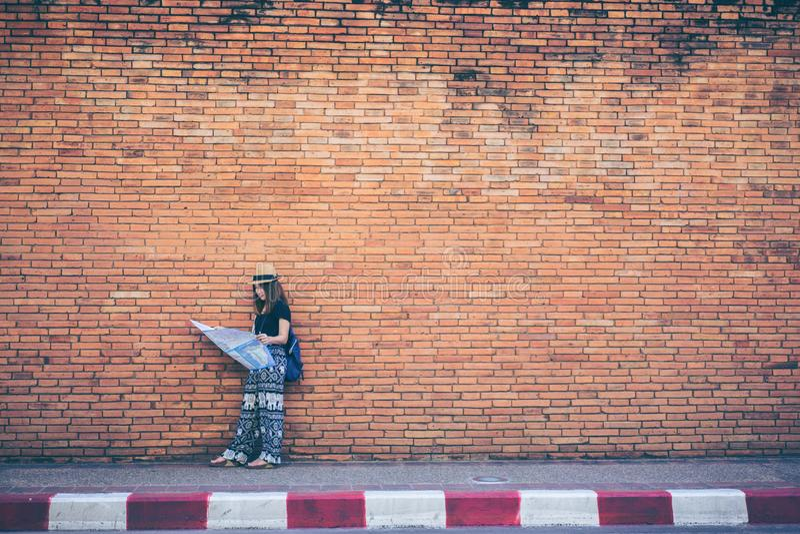 Giovane viaggiatore asiatico della donna con il cappello e borsa che esamina mappa Tha P fotografia stock libera da diritti