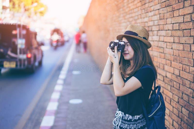 Giovane viaggiatore asiatico della donna con l'immagine della fucilazione della borsa e del cappello vicino fotografie stock