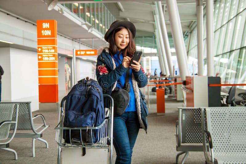 Giovane viaggiatore asiatico nei supporti caldi dei vestiti con le borse che esaminano lo smartphone il corridoio dell'aeroporto fotografia stock libera da diritti