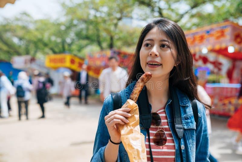 Giovane viaggiatore cinese unire la fiera del tempio di sakura in menta del Giappone salsiccia d'acquisto turistica della ragazza immagini stock libere da diritti
