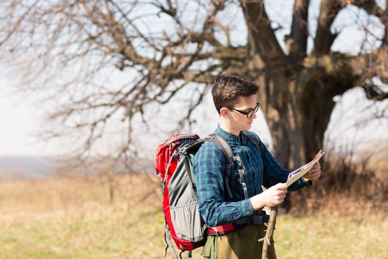 Giovane viaggiatore con lo zaino che esamina la mappa per le direzioni mentre facendo un'escursione nella campagna fotografie stock libere da diritti
