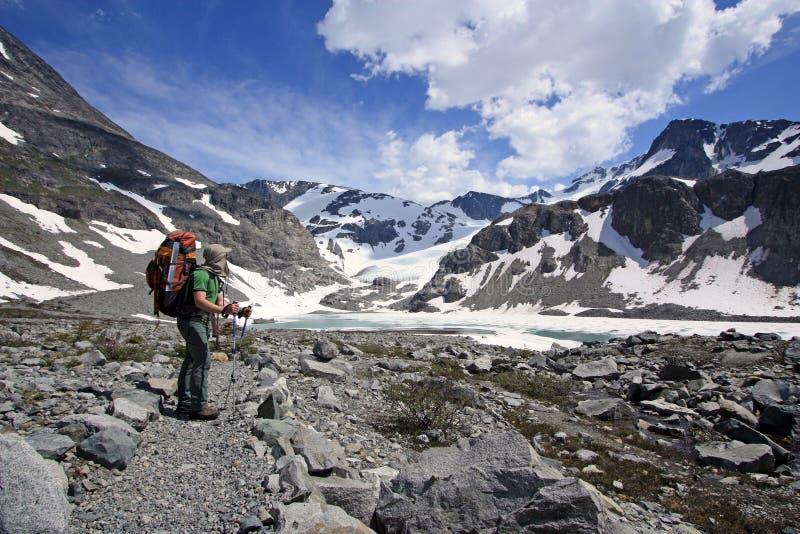 Giovane viaggiatore con zaino e sacco a pelo felice che gode dei Mountain View immagini stock libere da diritti