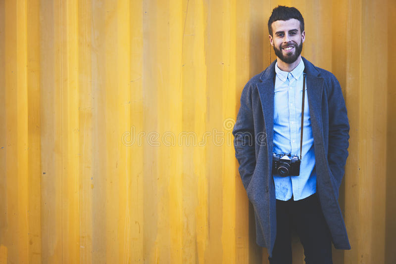 Giovane viaggiatore di blogger dei pantaloni a vita bassa in un rivestimento del denim che sta sul fondo variopinto della regolaz fotografia stock