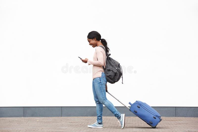 Giovane viaggiatore femminile afroamericano di profilo integrale che cammina con il cellulare e la valigia contro la parete bianc fotografia stock