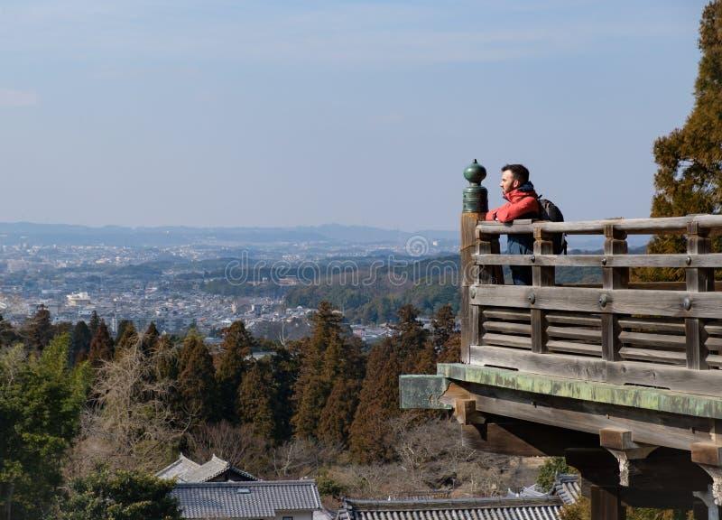 Giovane viaggiatore maschio che esamina città e paesaggio mentre travell fotografia stock