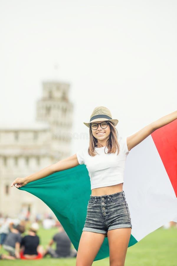 Giovane viaggiatore teenager della ragazza con la bandiera italiana prima della torre storica in città Pisa - Italia fotografia stock libera da diritti