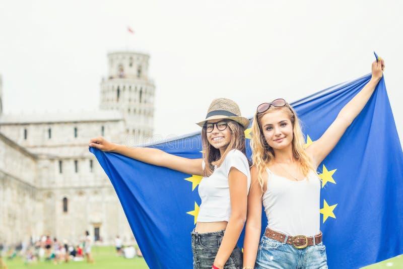 Giovane viaggiatore teenager delle ragazze con la bandiera di Unione Europea prima della torre storica in città Pisa - Italia fotografie stock