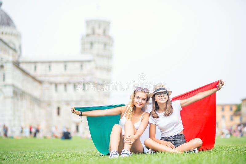 Giovane viaggiatore teenager delle ragazze con la bandiera italiana prima della torre storica in città Pisa - Italia fotografia stock