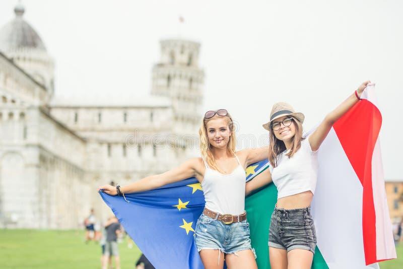 Giovane viaggiatore teenager delle ragazze con le bandiere di Unione Europea e dell'italiano prima della torre storica in città P immagine stock libera da diritti