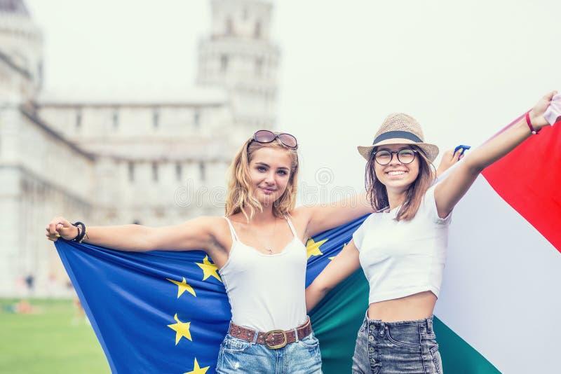 Giovane viaggiatore teenager delle ragazze con le bandiere di Unione Europea e dell'italiano prima della torre storica in città P immagini stock